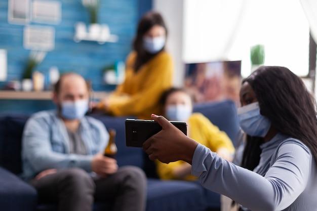 Groupe d'amis métis regardant une vidéo sur un smartphone, gardant une distance sociale en portant un masque facial comme mesure de sécurité contre l'infection par covid19 pendant la pandémie mondiale.