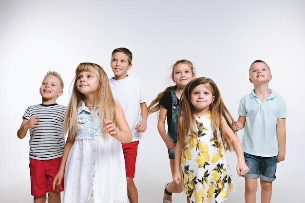 Groupe d'amis mignons d'enfants d'âge préscolaire de mode posant ensemble et regardant la caméra sur un fond de studio blanc. l'amitié, la mode, le concept d'été. espace pour le texte.