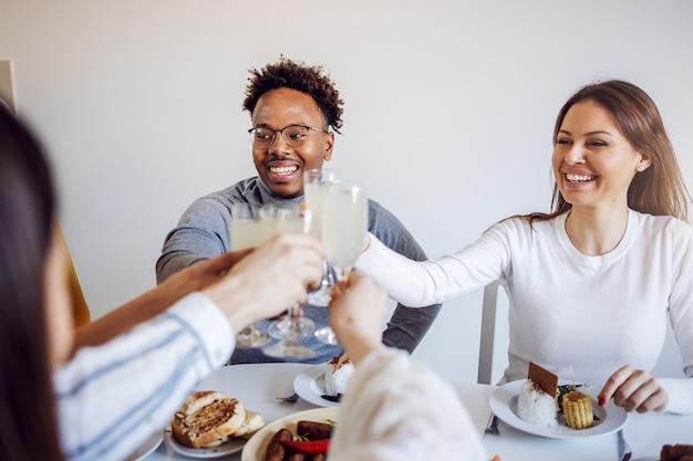 Groupe d'amis multiculturels assis à table pour le déjeuner et grillage avec de la limonade fraîche.