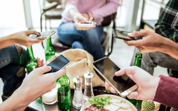 Groupe d'amis multiculturels s'amusant sur smartphone au bar