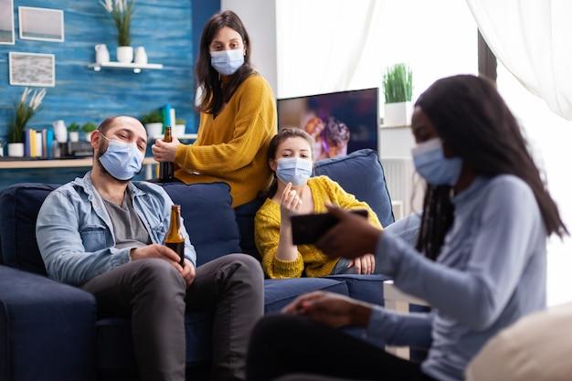 Groupe d'amis multiethniques traînant dans le salon en regardant un clip sur un smartphone assis sur un canapé en respectant la distanciation sociale portant un masque facial pendant la pandémie mondiale.