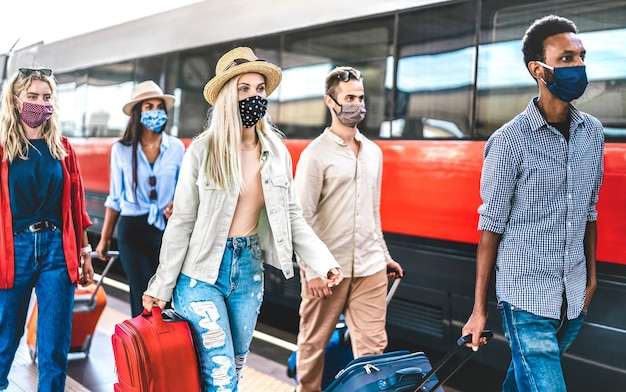 Groupe d'amis multiraciaux marchant au quai de la gare