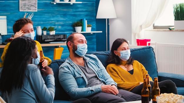 Groupe d'amis multiraciaux regardant une émission de comédie à la télévision en riant en profitant de passer du temps ensemble portant un masque facial pour prévenir l'infection par le covid 19 pendant la pandémie mondiale s'amuser assis sur un canapé