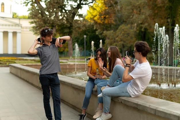 Groupe d'amis passant du temps ensemble à l'extérieur près de la fontaine
