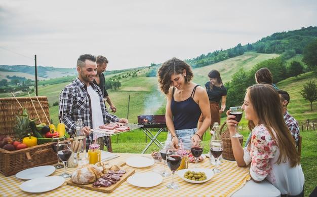 Groupe d'amis passant du temps à faire un pique-nique et un barbecue