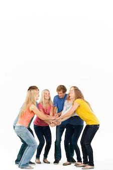 Groupe d'amis sur le point de se réjouir avec leurs mains empilés en souriant alors qu'ils se regardent