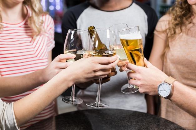 Groupe d'amis portant un toast avec de la bière et du vin