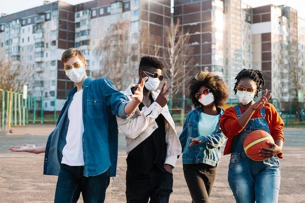 Groupe d'amis posant avec des masques chirurgicaux