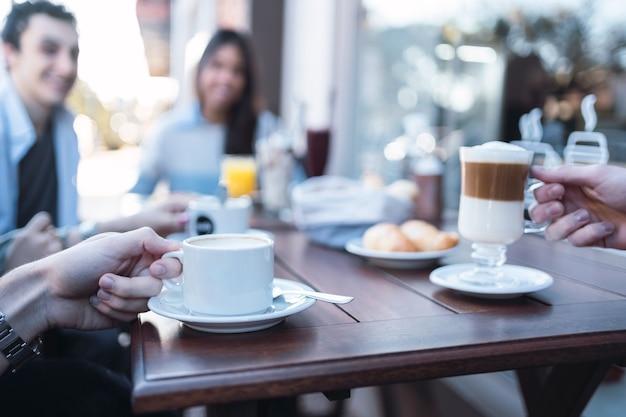 Groupe d'amis prenant le petit déjeuner dans un bar en plein air.