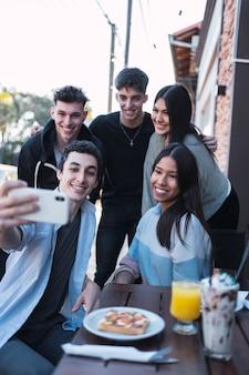 Groupe d'amis prenant une photo dans un bar extérieur .