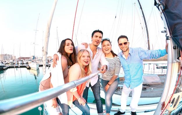 Groupe d'amis prenant une photo de selfie avec bâton lors d'un voyage de fête en bateau à voile de luxe