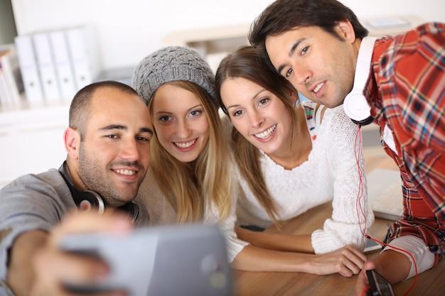 Groupe d'amis prenant des photos d'eux-mêmes avec smartphone