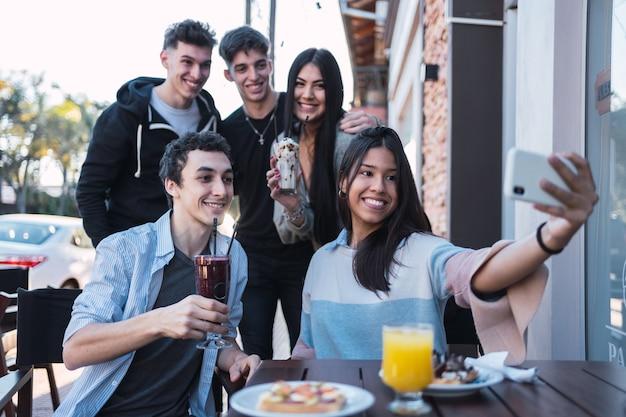 Groupe d'amis prenant un selfie dans un bar extérieur.