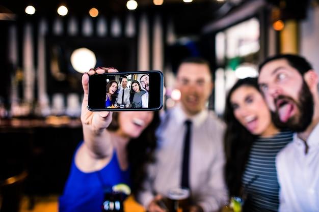 Groupe d'amis prenant un selfie dans un bar