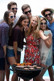 Groupe d'amis prenant un selfie près de la piscine