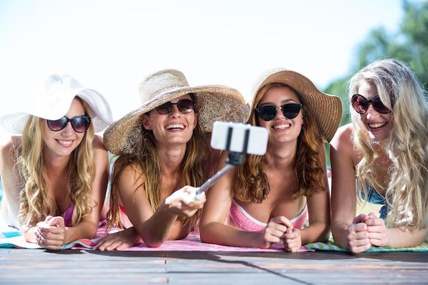 Groupe d'amis prenant selfie avec selfie stick