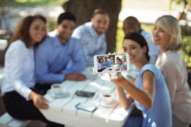 Groupe d'amis prenant selfie sur téléphone mobile
