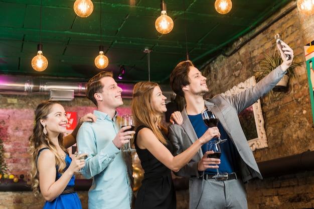 Groupe d'amis prenant selfie sur téléphone portable en soirée