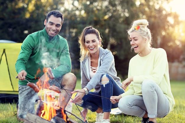 Groupe d'amis préparant des saucisses sur un feu de camp