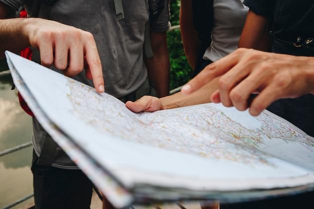Groupe d'amis qui regardent une carte voyagent ensemble