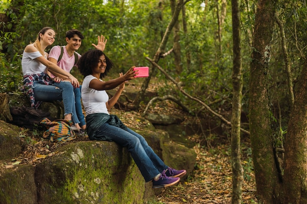 Groupe d'amis randonneurs assis sur un rocher prendre un selfie