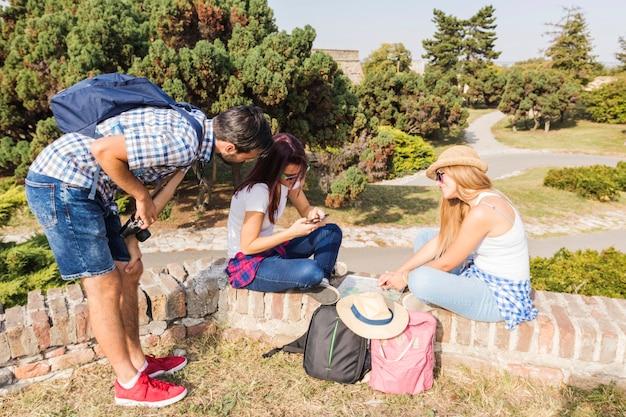 Groupe d'amis recherchant une direction sur un téléphone mobile