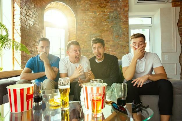 Groupe d'amis regardant le jeu à la télévision à la maison. les amateurs de sport passent du temps et s'amusent ensemble