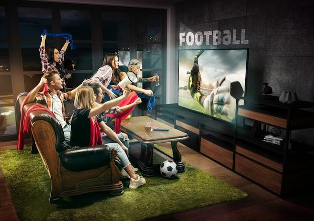 Groupe d'amis regardant des jeux de sport de championnat de match de télévision hommes émotionnels