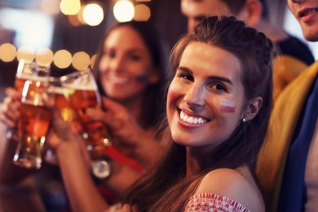Groupe d'amis regardant un match de football dans un pub