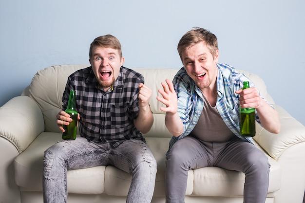 Groupe d'amis regardant le sport ensemble, les jeunes hommes boivent de la bière