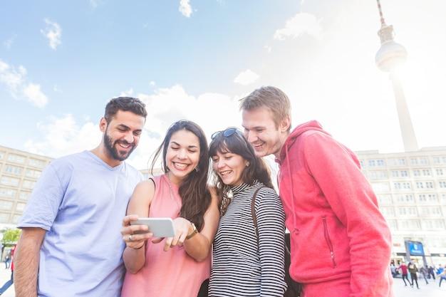 Groupe d'amis en regardant un téléphone intelligent à berlin