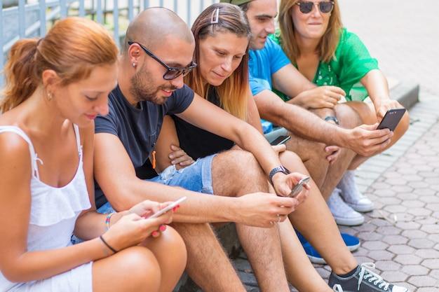 Groupe d'amis regardant des téléphones mobiles intelligents - génération millennials