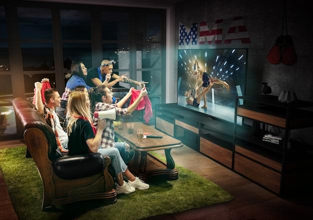 Groupe d'amis regardant la télévision, combat de mma aux états-unis, jeux de sport