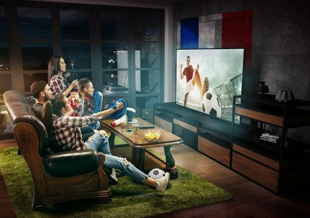 Groupe d'amis regardant la télévision, match, championnat, jeux de sport. des hommes et des femmes émotifs acclamant l'équipe de football préférée de france avec un drapeau. concept d'amitié, de sport, de compétition, d'émotions.