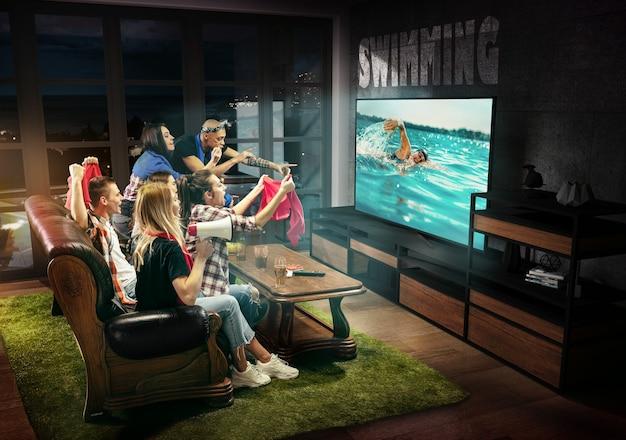 Groupe d'amis regardant la télévision, natation, championnat, jeux de sport. hommes et femmes émotifs encourageant le nageur préféré de l'équipe nationale. concept d'amitié, de sport, de compétition, d'émotions.