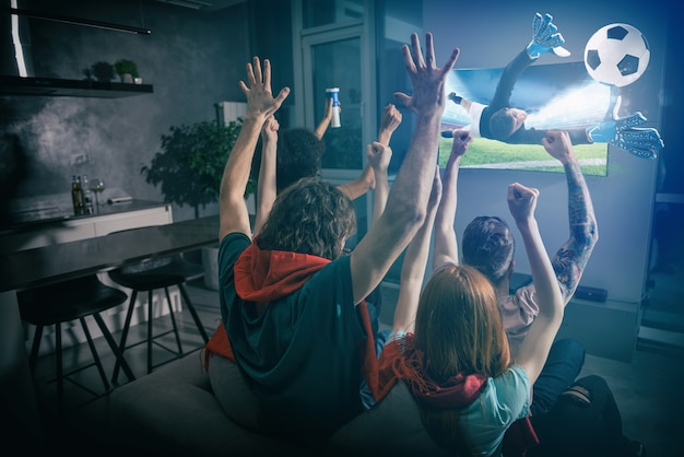 Un groupe d'amis regarde le match ensemble à la télévision et se réjouit