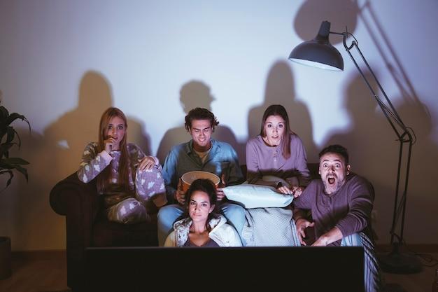 Groupe d'amis, regarder un film sur le canapé