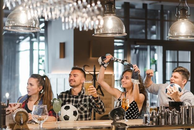 Groupe d'amis, regarder le sport ensemble dans le bar