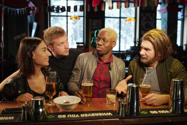 Un groupe d'amis a une réunion dans le pub, ils parlent et boivent de la bière