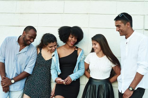 Groupe d'amis riant de quelque chose qu'ils regardent smartphone.