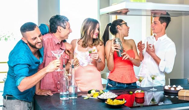 Groupe d'amis s'amusant au bar à cocktails de la maison avec apéritif avant le dîner à l'heure de l'happy hour