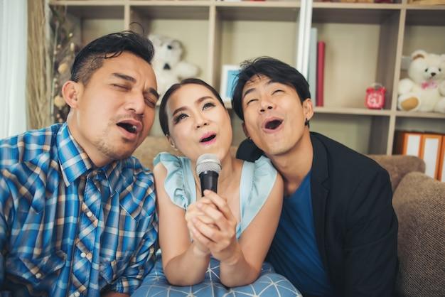 Groupe d'amis s'amusant au salon chantant une chanson ensemble