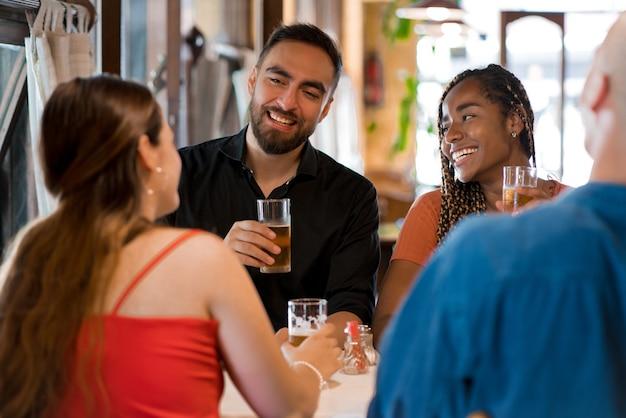 Groupe d'amis s'amusant ensemble tout en buvant un verre de bière dans un bar. notion d'amis.