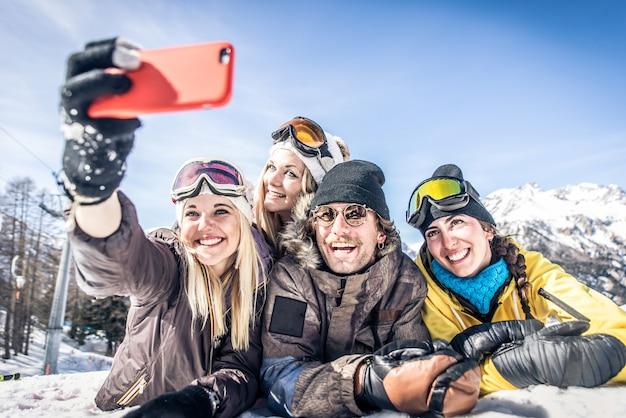 Groupe d'amis s'amusant sur la neige