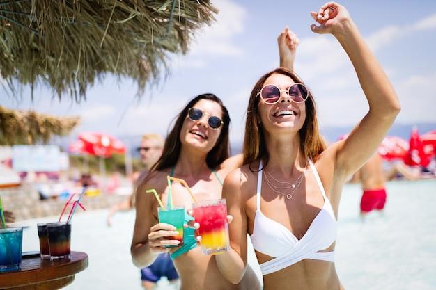 Groupe d'amis s'amusant pendant les vacances d'été et buvant des cocktails. concept de mode de vie, d'amitié, de voyage et de vacances des jeunes