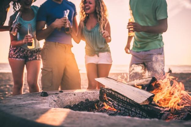 Groupe d'amis s'amusant sur la plage faisant un feu d'os