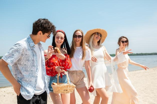 Groupe d'amis s'amusant sur la plage en journée d'été ensoleillée