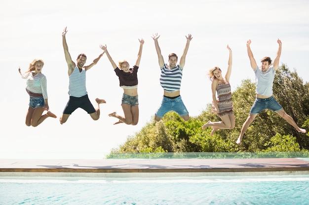 Groupe d'amis sautant au bord de la piscine