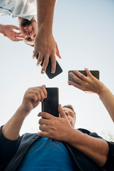 Groupe d'amis se détendre avec les smartphones à l'extérieur