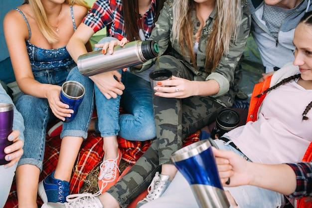 Le groupe d'amis se réchauffe avec du thé dans la tente. l'heure du pique-nique.